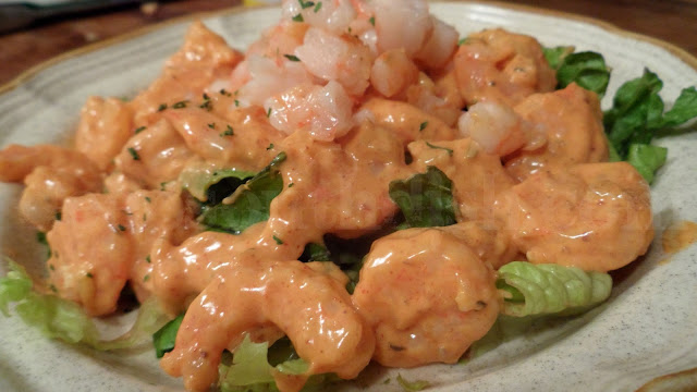 Cold cooked shrimp are dressed up with a tangy remoulade sauce and served over a bed of lettuce.