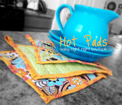 """3 hot pads next to a blue pitcher on two blue plates and titled, \"""" Hot Pads, baby night night boutique\"""""""