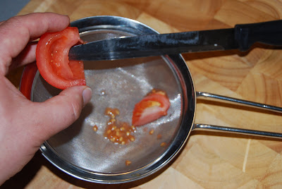 Tomato seeds being removed from the fruit using a knife and into a sieve