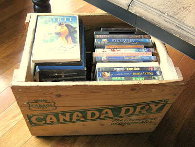 CDs and movies stored in a Canada Dry vintage crate underneath a coffee table for easy access.