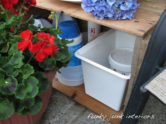 A crate on its side is used as a side patio table as well as storing pool equipment, chemicals and accessories.