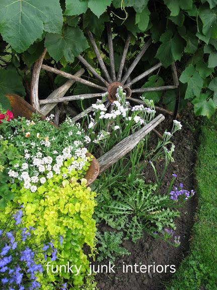 Learn how I used a vintage wagon wheel as a flower garden feature along with a wheelbarrow planter! Click for many other gardening tips included! #gardening #flowers #planters #gardenart