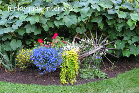 Learn how this wheelbarrow was turned into a beautiful planter garden feature! Click for many other gardening tips also included! #gardening #gardentips #flowers