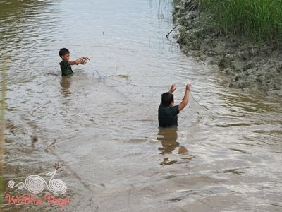 two boys in the river laying their fishing net