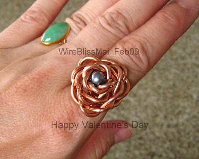 Wire wrapped rose ring with copper wire and pearl focal around finger