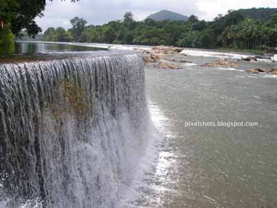 chalakkudy river photographed from thrissur district of kerala,small water falls in major water resource of kerala,water cascading through bunds built in keralas rivers