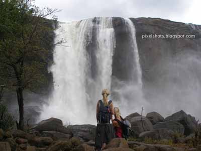 tourists watching athirapally waterfalls,kerala tourism,kerala tour destinations,waterfalls in kerala,7 wonders of kerala,athirapilly,tourism in kerala