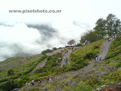 scenic mountain slope of munnar rajamala,people walking through the misty mountain road in munnar hill station kerala