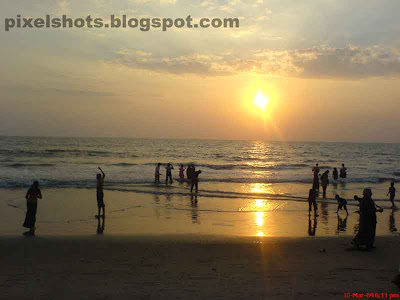 beach sunset photograph from calicut beach in kerala india,children playing in the beach during sunset a photograph taken with cell phone camera of 2 megapixel in landscape scenery shoot mode