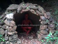 sculpture of man sitting inside a rock cave,thenmala sculpture garden photos,man sculptures