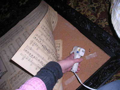 Turn and old picture into a bulletin board with vintage sheet music and old book pages.