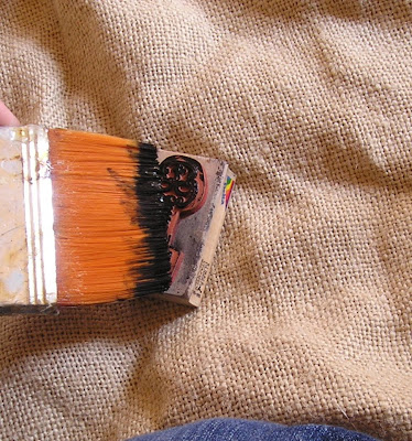 Paint acrylic paint onto stamp with a brush to stamp on burlap