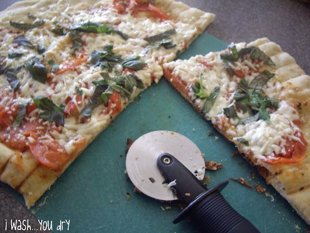 A pizza cutter slicing pizza on a cutting board.
