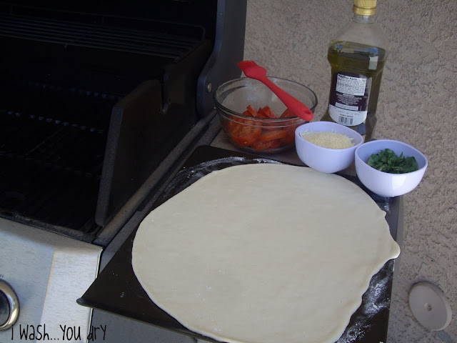 Pizza dough rolled out on a pan.