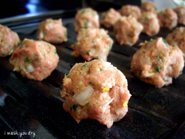 Raw meat balls on a pan.