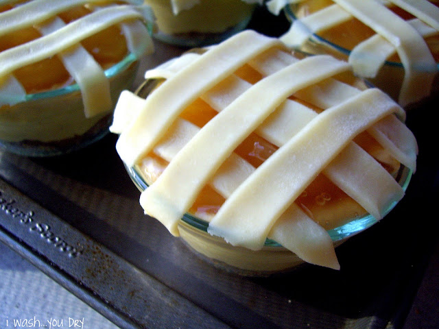 Strips of pie crust layer across the top of a small glass dish.