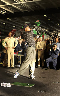 Sailors watch professional golfer Tiger Woods hit a few golf balls during a demonstration in the hanger bay of the nuclear powered aircraft carrier USS George Washington (CVN 73). U.S. Navy photo by Photographer's Mate 1st Class Brien Aho. (RELEASED)