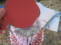 Glue a piece of felt, fabric, or scrapbook paper to the bottom of the can or jar to cover the plastic wrapper ends.