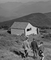 A photograph of men walking downhill by a small house.