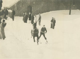 A black and white photograph of figures skiing.