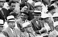 A black and white photograph showing a seated crowd of well-dressed men and women.