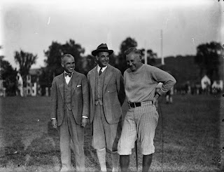 A black and white photograph of three smiling men standing together outside.