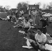 A photograph of several men and women seated and standing together on a lawn.