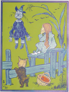 An illustration mostly in blue on a green backdrop, of a girl perched on a fence and looking at a scarecrow. A small dog also leans against the fence and there is a basket on the ground.