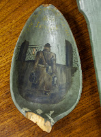The broken-off bowl of a spoon featuring a painting of a man from behind.