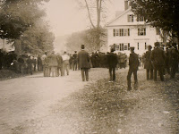 A photograph of a crowd from behind, standing outside.
