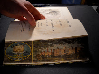 A bent fore edge, revealing Hampton Palace and a portrait of Henry VIII.""
