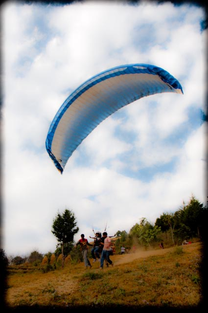 Paragliding @ Naukuchiataal, Uttrakhand state of INDIA : During recent trip to Naukuchiataal, all of our office folks tried Paragliding and it was a great fun... Its 6 kilometers form the lake and one has to trek 400 meters to take off for the flight :): Here is our first hero to take the flight in the air.. Paraglider take off from a cliff and land down in a village near to the lake... Its 15-20 minutes ride depending upon the flow of the air... They charge 1300 rs for that.. I had already done paragliding at SONLANG Valley near Manali in Himachal Pradesh and BIR BILLING in Kangra Valley... So it was not worth spending 1300 .. For first time experience, its worth... Also one can negotiate to get a deal for 800-1000 in case group comprises of more than 5... : After feeling the excitment, most of my friends tried a ride in air... during the ride, many of them thought that I am clicking their photographs ... and you know... there was no pic with clear face :( : One of our friend screaming while taking off for the flight in air.... Road connecting lake and the place where paragliding happens... This road was very beutiful and had few patches on the way...Coloful hills arond paragliding area at Naukuchiataal... This is a view of hills parallel to the place where paragliders take off.... Tarun and his family taking rest on the half way while climbing to paragliding club.... Another photograph of the road leading to Pragaliding place from Naukuchiataal.. All of them want to try paragliding and waiting for gliders to come back.... Actually there were only 5 gliders there and they used to take them back from the landing place... All this used to take 30 minutes at least... A view of the lake from Paragliding place @ Naukuchiataal, Uttrakhand, INDIA... This is the landmark to find out the place where paragliding happens in Naukuchiataal... When we were driving towards it, we moved ahead and missed this board.... after some distance, we asked a gentleman on the way and got to know that borad was the point form where we had to climb to a small hill... Another paraglider in sky with clouds @ Naukuchiataal, Uttrakhand, INDIA