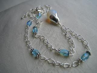 293cd464614 Hõbedase kaelaketi ripatsi kivi on helesinise/valge kumaga opaal, lisaks  lihvitud klaaspärlid. OPAAL - Vett sisaldav ränidioksiid.