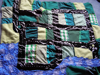 A playmat made of green fabric and ribbon with black PVC roads