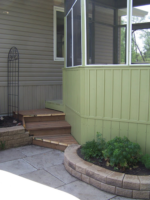 Steps from deck to patio with stacked stone planters