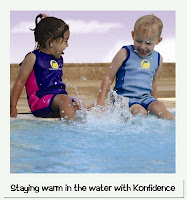Image of two children, a girl and a boy kicking the pool water in kids wetsuits