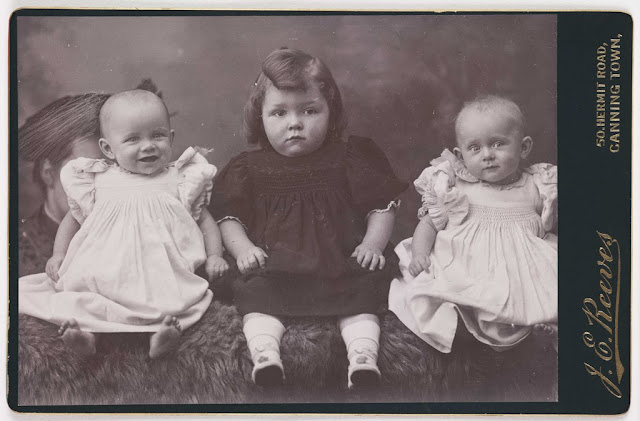 A cabinet card of three children. J E Reeves; Cabinet Card. Collection of National Media Museum. A woman, probably their mother, can be seen behind them. photography-news.com, photography news, Diana Topan, International Children's Day, June 1, vintage baby photos