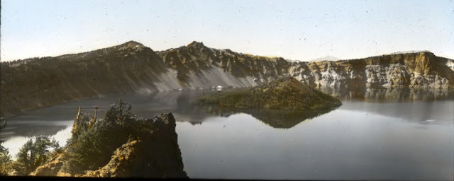 """Image Title: Wizard Island in Crater Lake Image Description: """"A close view of Wizard Island in the lake near the west shore. It is a perfect little volcano – a crater within a crater. Although a few pines are growing upon it, the island's lava and ashes appear as if just cast from the internal furnace. The island rises several hundred feet above the lake-surface, and it's crater is eighty feet deep. The island is a good view-point at noon, at evening, or when the blue cold crater glows and sparkles with the reflected fires of a million fiery worlds."""" Original Format: Lantern slides Original Collection: Visual Instruction Department Lantern Slides. photography-news.com, Photography News, Diana Topan, Crater Lake, Oregon photos, landscape photography"""