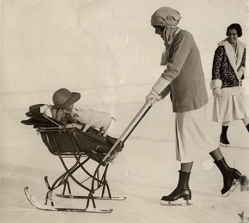 Pram on skis (sledge) on the ice, pushed by mom on skates. St. Moritz, Switzerland, 1926. Nationaal Archief / Spaarnestad Photo