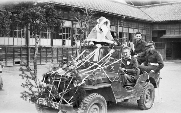 "Christmas at Miyajima School, 1946. Itsukushima, Japan. During the Christmas activities organised by 116th Australian construction depot, British Commonwealth Occupation Force (BCOF), at Miyajima school Santa Claus arrives by jeep. On the front of the jeep, inscribed in Japanese, are the words ""Merry Christmas"". Left to right: VX150376 driver a. R. Davis, Euroa, Vic (1); SX34345 private M. P. Burgess, Norwood, SA (2); NX196391 Private C. R. Ansell, Willoughby, NSW (3)"