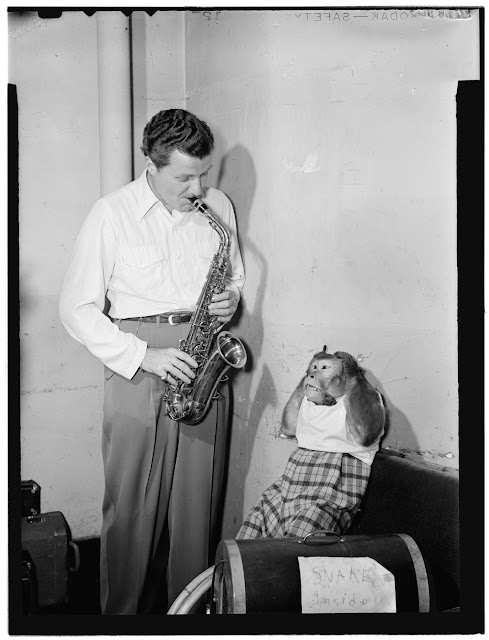 "Portrait of Charlie Barnet and Re-Bop, New York, N.Y., ca. Aug. 1946. Caption from Down Beat: Charlie Barnet's pet monkey, Re-Bop, pretends that he doesn't find much harmony in the sax tootlings of his maestro on the cover of this issue. But it's all in fun, and the grimaces of the monkey are not the reason that Charlie is breaking up his dance band early this month. He's going out to California to rest for the remainder of the summer, probably will re-organize on the west coast this fall. Forms part of: William P. Gottlieb Collection (Library of Congress). In: ""Charlie, Re-Bop on the cover,"" Down Beat, v. 13, no. 17 (Aug. 12, 1946)."