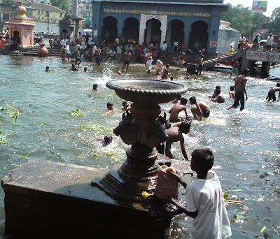 A boy collects holy waters of the river Godavari in Nashik