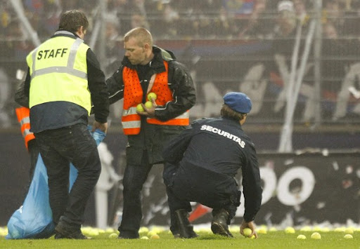 Members of the security collect tennis balls thrown by FC Basel supporters on the pitch