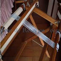 Foto mostrando os fios do urdume já montados em um Tear de Pente Liço