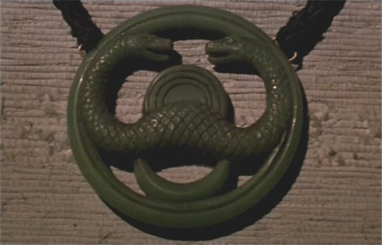 Mimicking The Other Acolytes As He Gives Distinctive Two Handed Snake Salute And Displays Stolen Jade Cult Amulet
