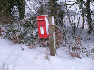 Snow covers a Royal mail postbox