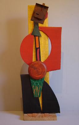 Escultura-ensamblaje de madera con cartones pintados en acrílico, cuero y cerradura