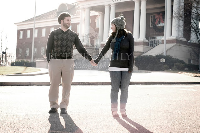Wide shot of couple holding hands with Roswell City Hall in the background