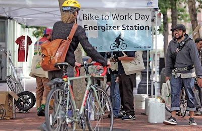 People stop at a booth dedicated to Bike to Work Day at Battery and Market Streets in San Francisco