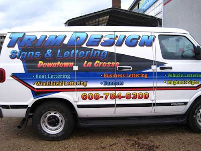 Full-size van with lettering advertising a business called Trim Design Signs & Lettering. Super ugly!